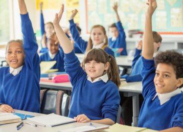 Elementary school children wearing blue school uniforms raising hands in classroom. Image shot 2014. Exact date unknown.